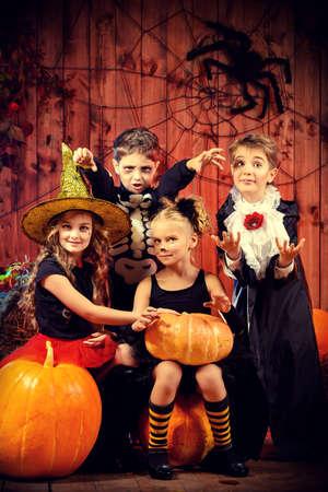 calabazas de halloween: Niños alegres en disfraces de halloween que celebran Halloween en un granero de madera con calabazas. Concepto de Halloween.