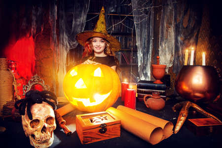 the enchantress: Beautiful little girl in a costume of witch in a wizarding lair. Halloween party. Halloween decorations.