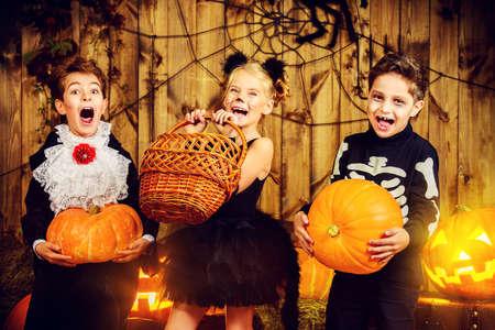 calabazas de halloween: Grupo de ni�os alegres en trajes de halloween posando juntos en un granero de madera con calabazas. Concepto de Halloween. Foto de archivo