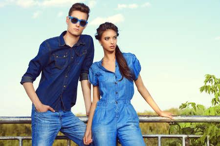 mezclilla: Moda foto de una pareja joven y atractiva en ropa de jeans posando al aire libre.