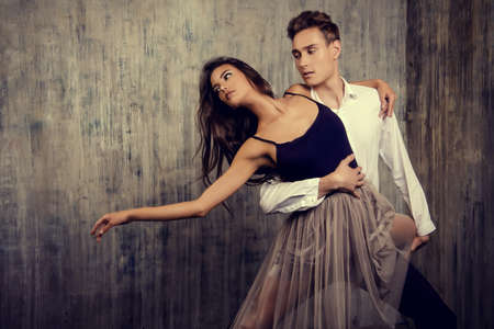 ballroom dancing: Beautiful couple of ballet dancers dancing over grunge background. Beauty, fashion.