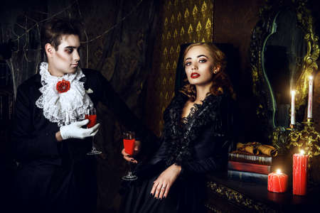 medieval: Beautiful man and woman vampires dressed in medieval clothing stand in a room of the old abandoned castle. Halloween.