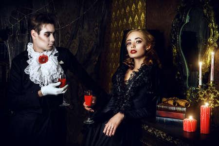 satan: Schöne Mann und Frau Vampire in mittelalterlichen Gewändern stehen in einem Raum der alten, verlassenen Burg. Halloween.