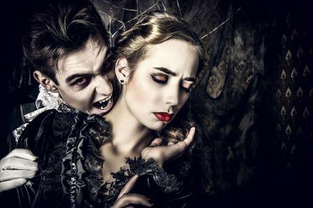 Vampiro masculino sanguinario vestido medieval está mordiendo a una bella dama. Halloween.