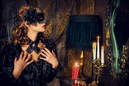 Okouzlující tajemná dívka v černé masce a černé středověké šaty stojí v zámeckém obývacím pokoji. Upír. Halloween koncept. Vintage styl.
