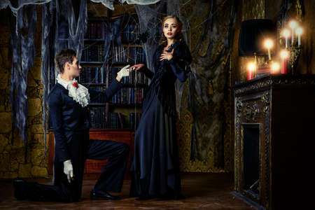 vampire: Beautiful man and woman vampires dressed in medieval clothing stand in a room of the old abandoned castle. Halloween.
