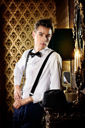 handsome young man: Elegant young man stands by the fireplace in a room with classic interior