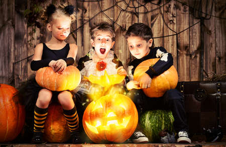 Grupo de niños alegres en trajes de halloween posando juntos en un granero de madera con calabazas. Concepto de Halloween. Foto de archivo