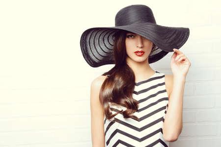 Retrato de una hermosa mujer elegante en elegante sombrero de ala ancha