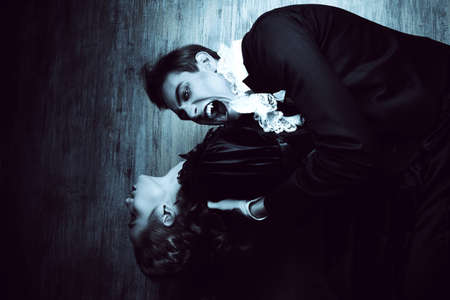 dracula woman: Bloodthirsty male vampire in medieval dress is biting a beautiful lady. Halloween.