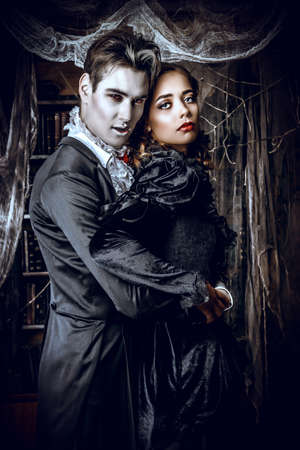 donne eleganti: Belle uomo e donna vampiri vestiti in abiti medievali stare in una sala del vecchio castello abbandonato. Halloween.