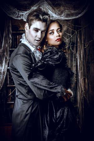 mujeres elegantes: Hermosas vampiros hombre y mujer vestidos de medieval de pie en una habitación del antiguo castillo abandonado. Halloween.