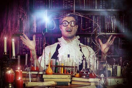 medieval: Viejo hombre loco científico medieval trabajando en su laboratorio. Alquimista. Halloween.