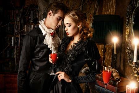 diavoli: Belle uomo e donna vampiri vestiti in abiti medievali stare in una sala del vecchio castello abbandonato. Halloween.