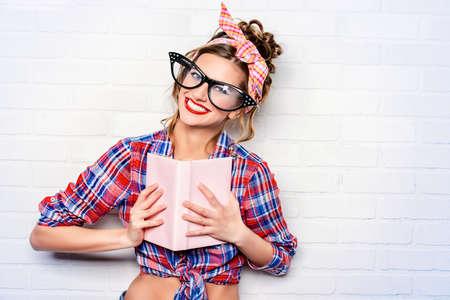 mujer elegante: Funny girl pin-up glamoroso en elegantes gafas enormes de leer un libro. Foto de archivo