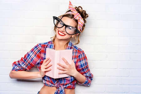 Funny glamorous pin-up girl in elegant huge glasses reading a book.