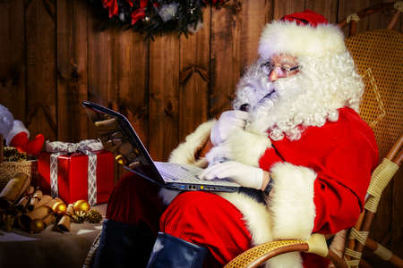 nicholas: Modern Santa Claus at his wooden house working on his laptop and smoking a pipe. Christmas. Stock Photo