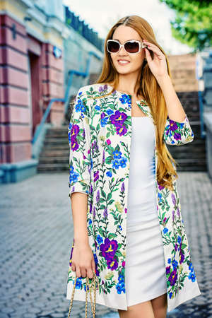 glasses model: Fashionable young woman walking on a city street and smiling. Stock Photo