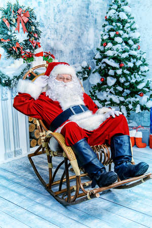 claus: Good old Santa Claus sitting in a rocking chair in the room by the fireplace and Christmas tree, beautifully decorated for Christmas.