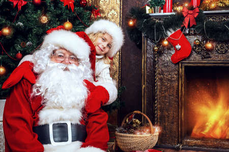 claus: Happy little girl sitting with Santa Claus and rejoice a gift. Christmas decoration.