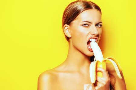Joven mujer de comer plátano divertido. Frutas tropicales. Concepto del verano. Alimentación saludable.