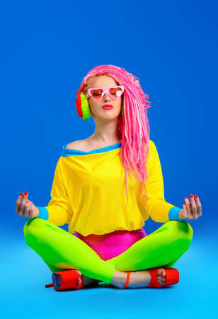 Trendy bright girl listening to music in headphones and meditating. Disco, party. Show business. Bright fashion. Stock Photo