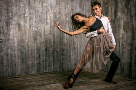 taniec: Piękna para tancerzy baletowych tańczących na tle grunge. Uroda, moda.