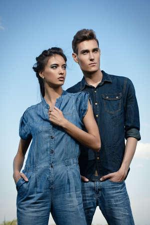 modelos hombres: Retrato de una moderna jóvenes que vestían ropa de jeans en el cielo azul. Disparo de moda. Foto de archivo