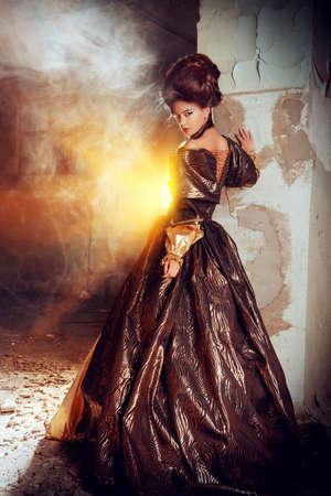 Art Fashion. Krásná mladá žena v elegantní historické šatech as barocco updo účes pózuje v ruinách hradu. Renaissance. Barocco.