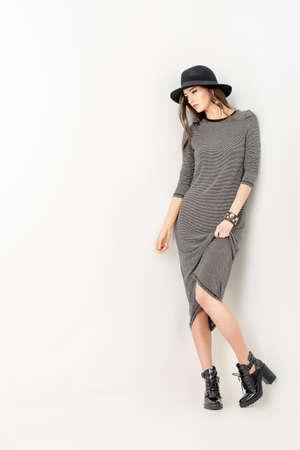 moda: Studio foto de una mujer joven magnífica en un vestido apropiado y elegante sombrero clásico. Foto de archivo