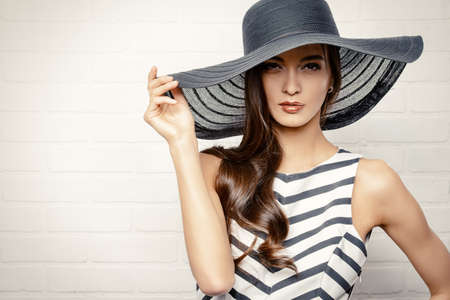white hat: Portrait of a beautiful graceful woman in elegant hat with a wide brim.