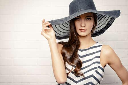 ropa de verano: Retrato de una hermosa mujer elegante en elegante sombrero de ala ancha.