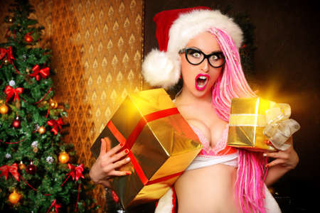 alluring: Pretty sexy girl wearing pink lingerie and pink hair alluring in the Christmas decoration. Stock Photo