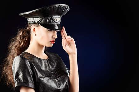 militaire sexy: Sexuelle jeune femme séduisante en costume de cuir approprié et une casquette de l'agent de police. Beauté, mode.