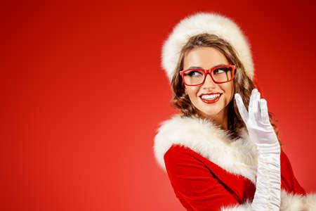 Reizvolle junge Frau in Santa Claus Kleidung und elegante rote Brille. Red Hintergrund. Weihnachtsfeier.