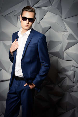 Fashion shot of a handsome young man in elegant classic suit and sunglasses. Stock Photo