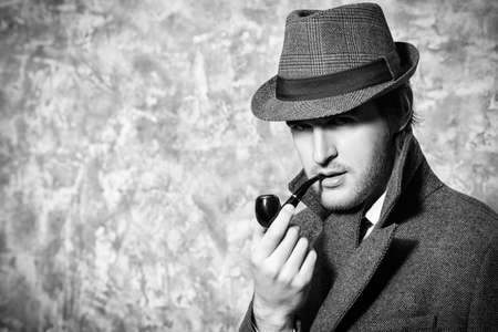british people: Handsome young man wearing classic hat and a coat smokes a pipe. Beauty, fashion. Stock Photo