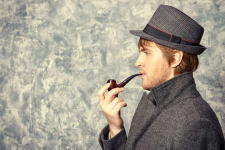 Handsome young man wearing classic hat and a coat smokes a pipe. Beauty, fashion. Side view. Stock Photo