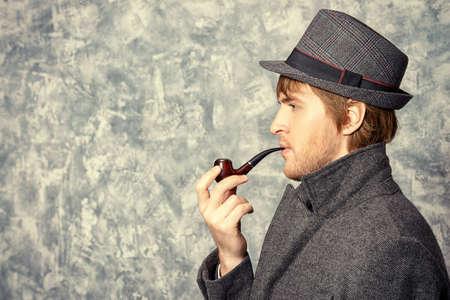 hombre con sombrero: joven hombre que usaba sombrero clásico y un abrigo fuma un tubo. Belleza, moda. Vista lateral.