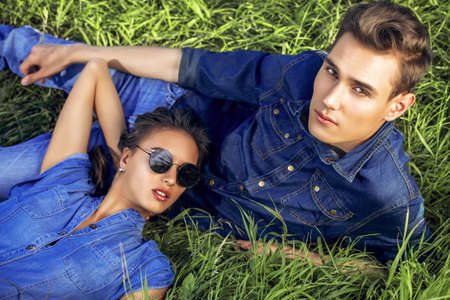 hair man: Attractive young couple wearing jeans clothes lying relaxed on a grass. Fashion shot.