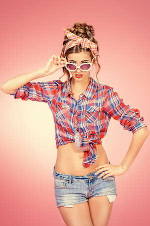 shorts: Pretty pin-up girl alluring in shorts and shirt over pink background. Beauty, fashion. Optics, eyewear. Stock Photo