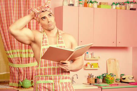 householder: Handsome muscular man in an apron studies a cookbook in the pink kitchen. Love concept. Valentines day. Womens day.