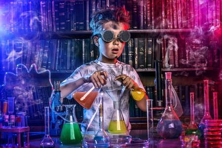 Chlapec dělá pokusy v laboratoři. Výbuchu v laboratoři. Věda a vzdělávání.