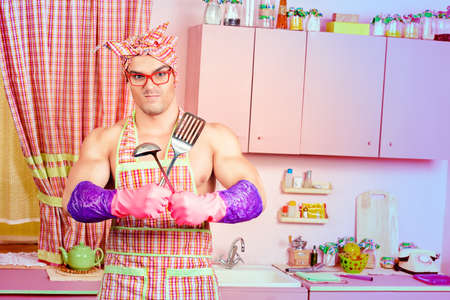 fun day: Attractive muscular man in an apron posing with a ladle with expression. Family, love concept. Valentines day. Womens day.