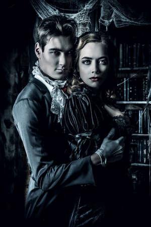 castello medievale: Belle uomo e donna vampiri vestiti in abiti medievali stare in una sala del vecchio castello abbandonato. Halloween.