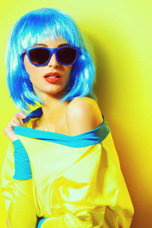 vivid: Bright glamorous girl in vivid clothes and a wig alluring over green background. Beauty, fashion. Cosmetics, hairtsyle. Optics, eyewear. Stock Photo