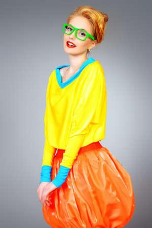 vivid: Glamorous fashion model posing in vivid colourful clothes and glasses. Bright fashion. Optics, eyewear. Studio shot.