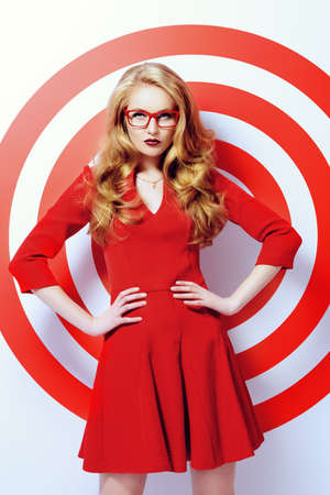 Beleza: Modelo de forma lindo no vestido vermelho e elegantes óculos vermelho que levanta sobre círculos vermelhos do alvo. Beleza, moda. Óptica, óculos. Imagens