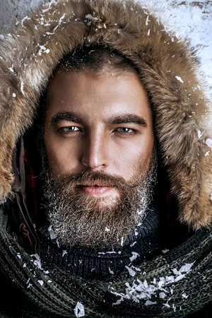 frost covered: Portrait of a handsome brutal man with beard and mustache dressed in winter clothes, covered with frost. Stock Photo