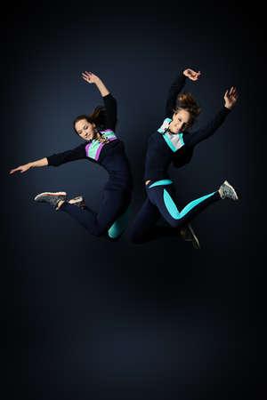 ropa deportiva: Dos mujeres jóvenes en ropa deportiva de saltar de alegría. Estudio sobre fondo negro.
